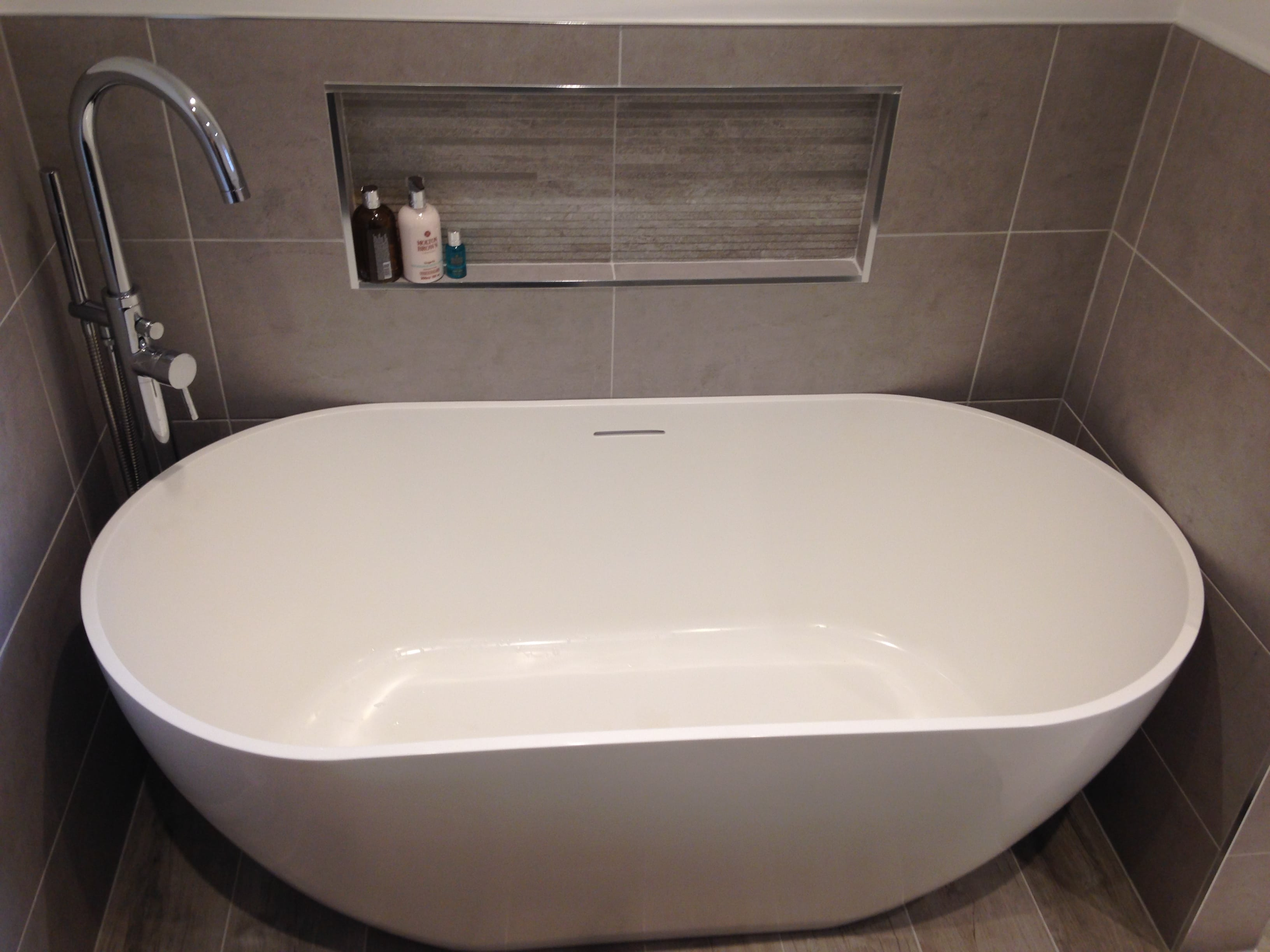 Bathroom installation freestanding bath with grey tiles behind